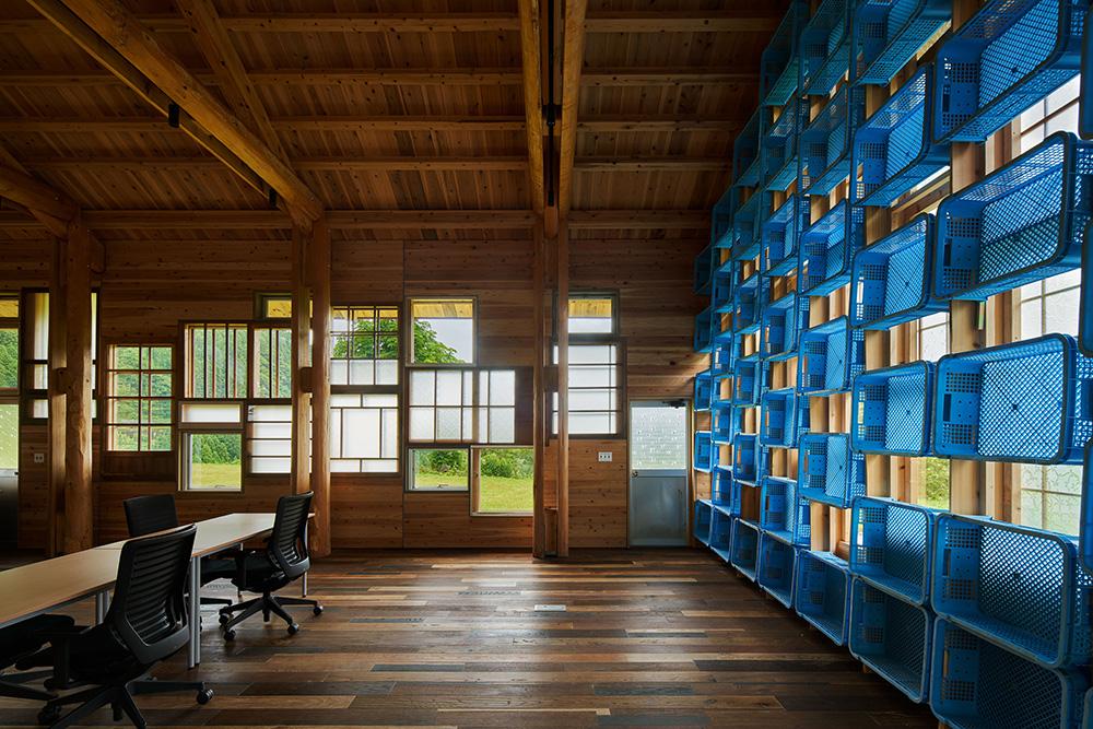 町営のシイタケ工場の収穫かごを再利用したガラス方建ての座屈止めを兼ねた本棚。 photo