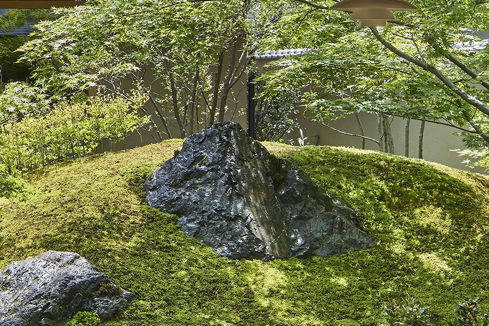 笏谷石の磐座。植木は葉が小さく盆栽仕立てのものを林のように植えている。 photo
